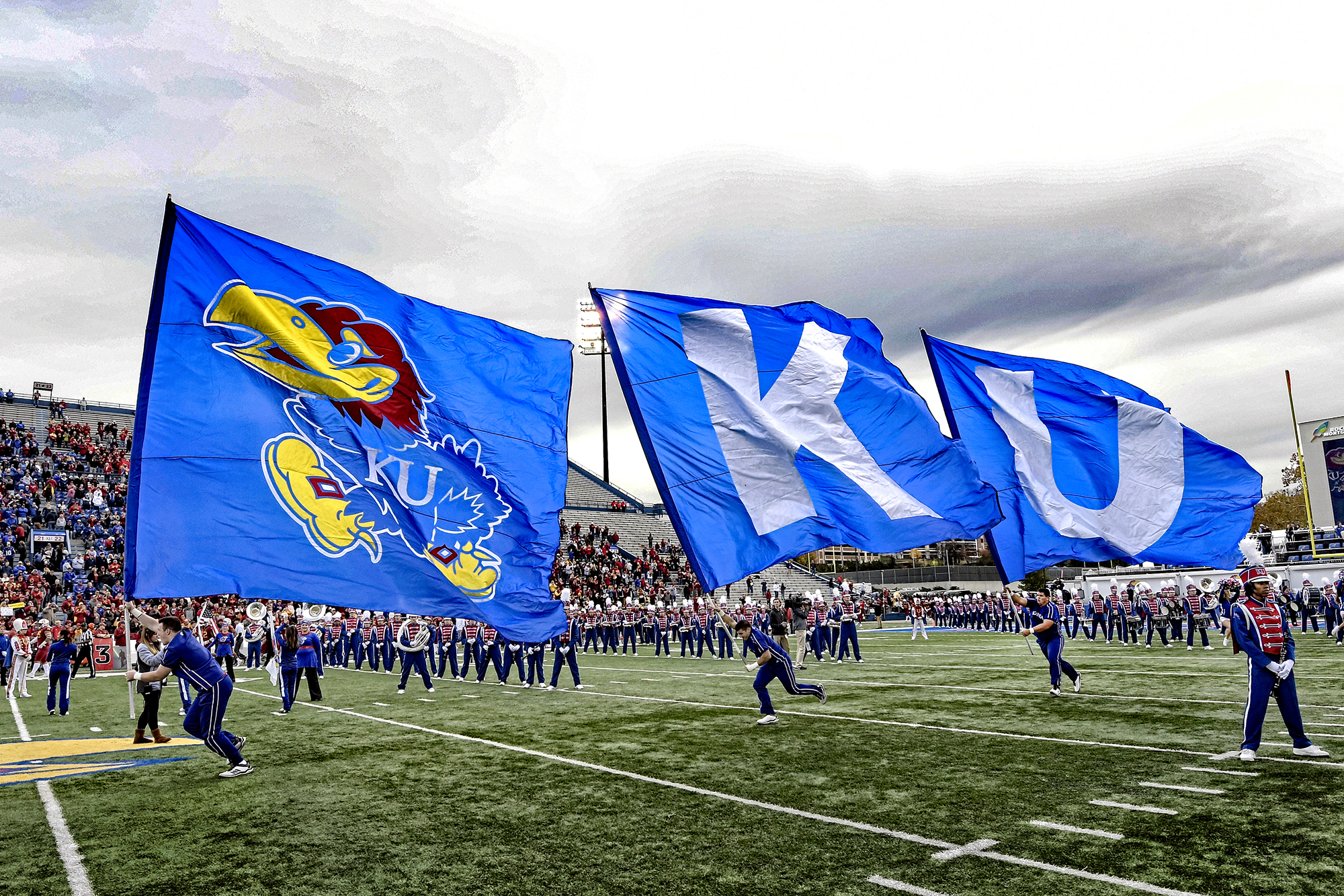 FLAG BEARERS – KU cheerleaders Zack Brenner, Max Simonian and Caleb Locke used all their speed and strength to lead the KU football team onto the field while bearing three large flags inside David Booth Kansas Memorial Stadium where the Jayhawks played Iowa State on Saturday, November 3.